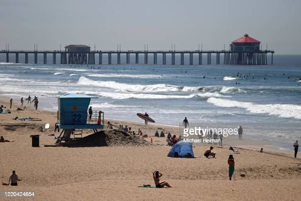 People and surfers are seen on the beach on April 22 2020 in Huntington Beach California Southern California is expecting summer like weather over...