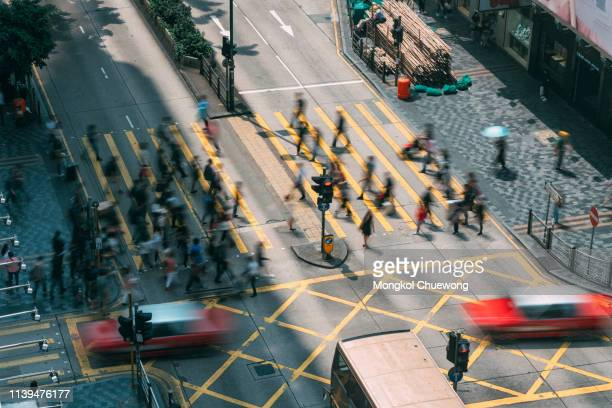people and taxi cabs crossing a very busy crossroads in tsim sha tsui district hong kong, china - tsim sha tsui stock pictures, royalty-free photos & images