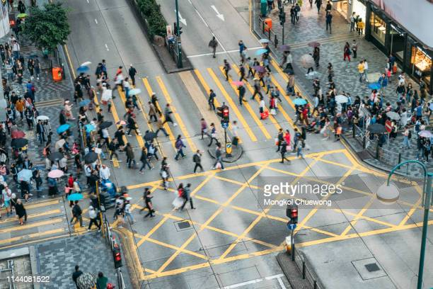 people and taxi cabs crossing a very busy crossroads in tsim sha tsui district hong kong, china - central stock pictures, royalty-free photos & images