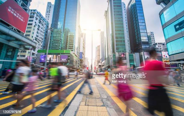 people and taxi cabs crossing a very busy crossroads in tsim sha tsui district hong kong, china - stock photo - hong kong stock pictures, royalty-free photos & images