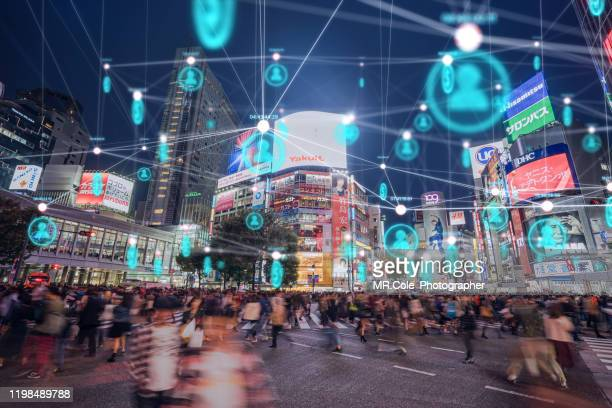people and technology concept,global communication icon with network connections line above crowded people walking .internet of things and smart city concept,technology-futuristic concept - wireless technology fotografías e imágenes de stock