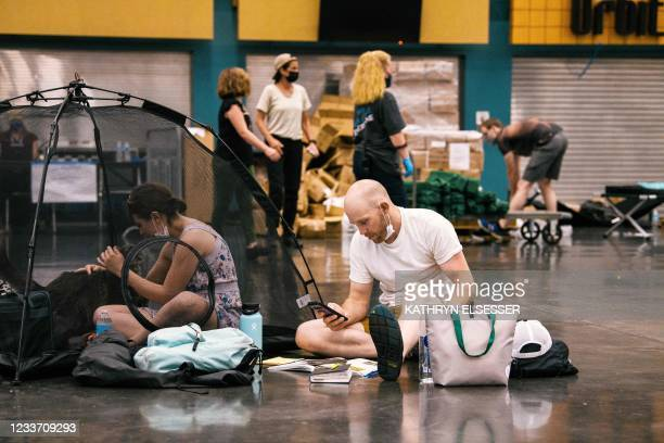 People and their pets rest at the Oregon Convention Center cooling station in Oregon, Portland on June 28 as a heatwave moves over much of the United...