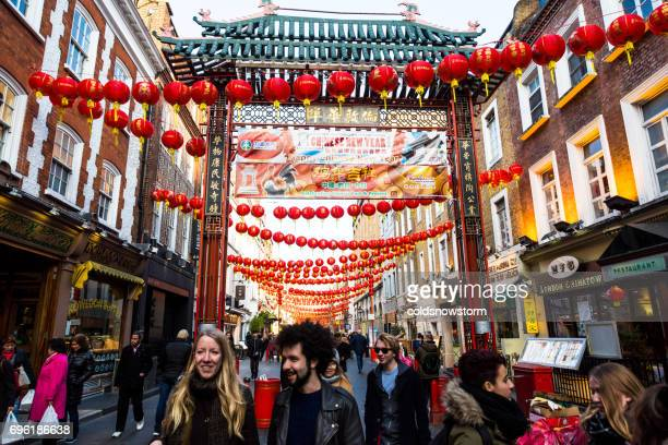 People and tourists walking with red lanterns in background, Chinatown, London, UK