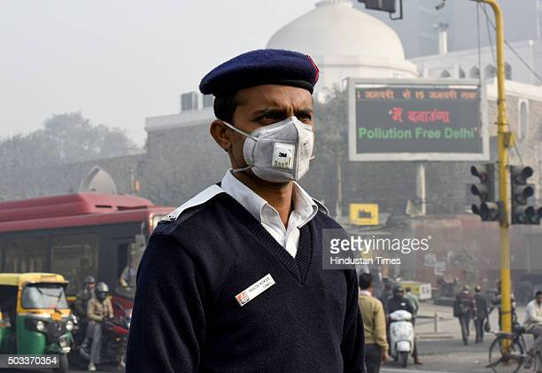 People and traffic police wearing a mask during the implementation of oddeven vehicle formula at ITO crossing on January 4 2016 in New Delhi India...