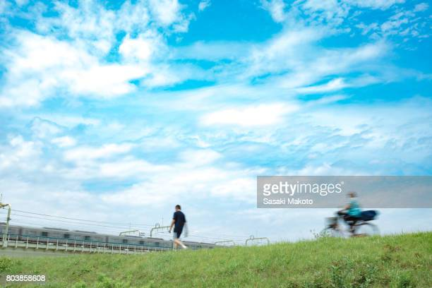 people and trains passing by during daytime in summer - riverbank stock photos and pictures