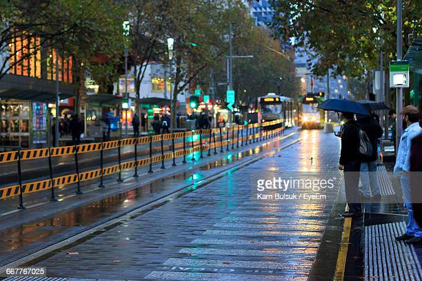people and vehicles on city street in monsoon - rain stock pictures, royalty-free photos & images