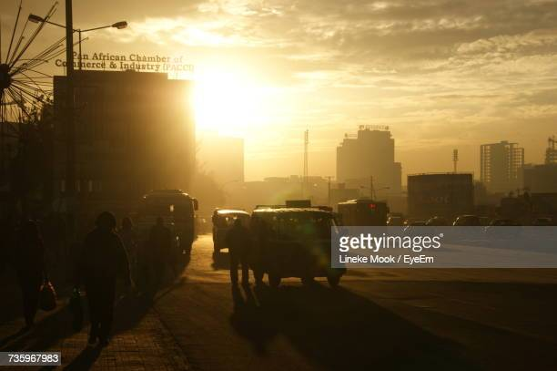 People And Vehicles On Street In City Against Cloudy Sky During Sunset