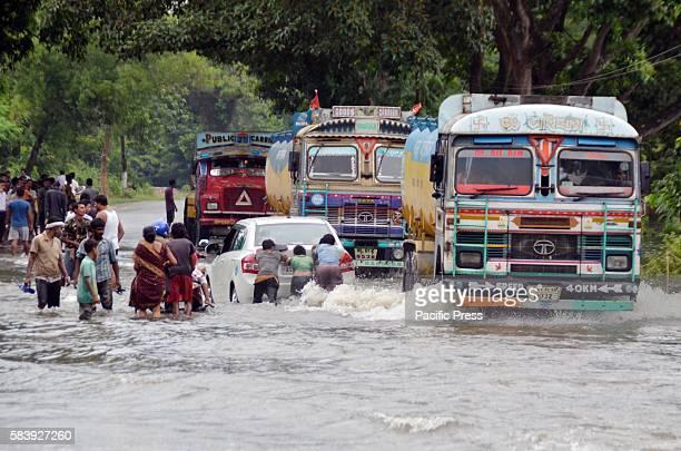 KAZIRANGA NAGAON ASSAM INDIA People and vehicles wading through flood water on a submerged road of Kaziranga in Nagaon district of Assam India today...