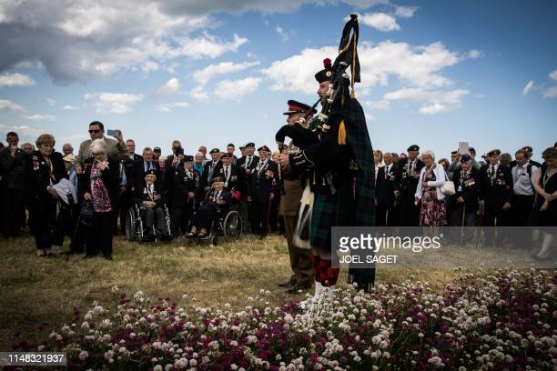 TOPSHOT People and veterans watch as a British soldier plays the bagpipes in Arromanches Normandy during the inauguration of a garden as part of the...