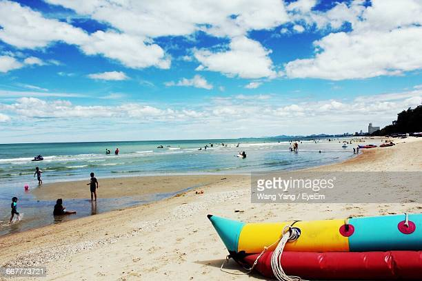 People And Water Sled At Beach Against Cloudy Sky