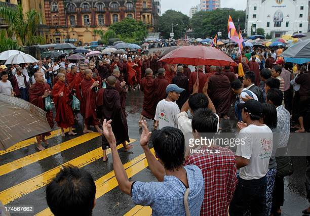 People applaud as Burmese Buddhist monks protesting against the military junta are gathering near the Sule pagoda one of the most popular in Rangoon