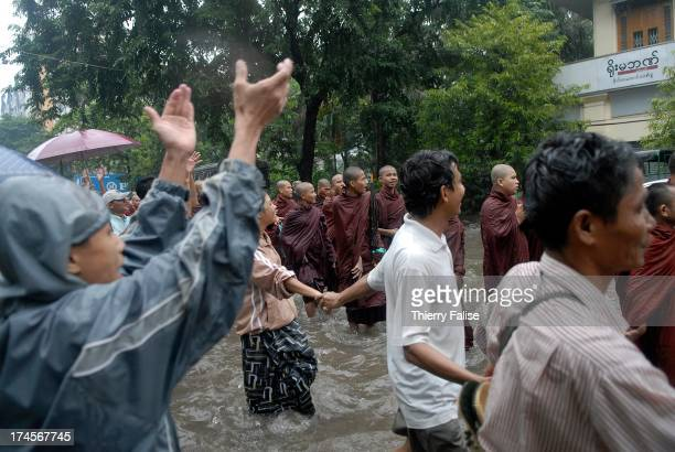 People applaud as Burmese Buddhist monks protesting against the military junta are marching in the streets of Rangoon..