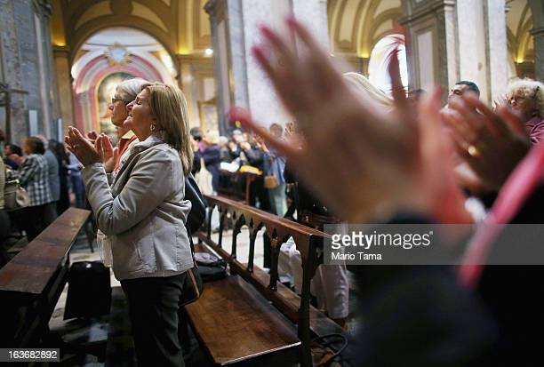 People applaud in the Metropolitan Cathedral at the conclusion of Mass on the day after Pope Francis formerly Cardinal Jorge Mario Bergoglio was...