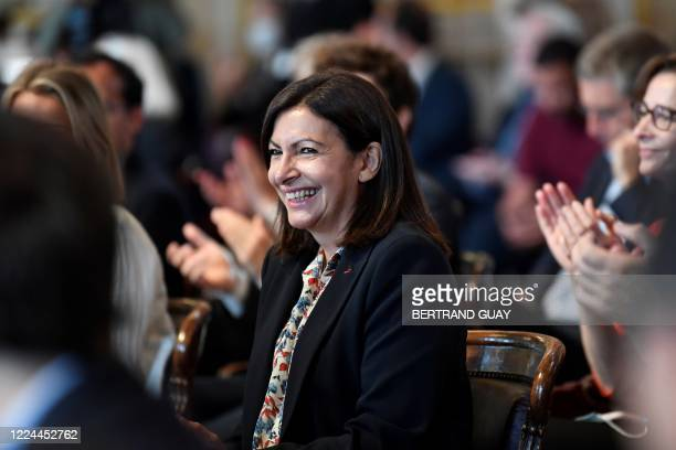 People applaud Paris' Mayor Anne Hidalgo upon her arrival on July 3 2020 at the Paris city hall in Paris for the Paris council meeting that will...