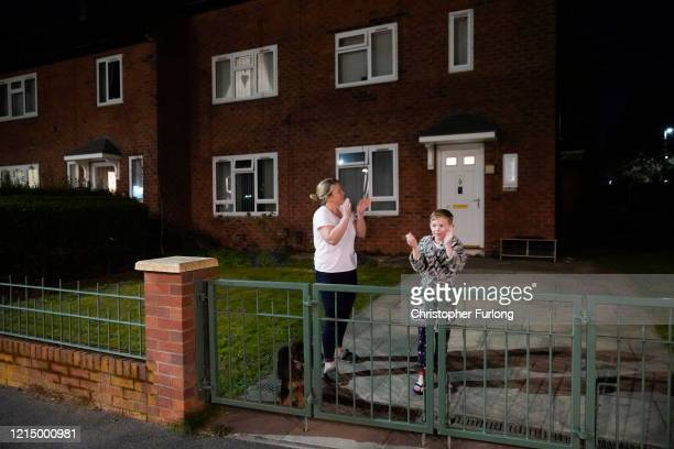 People applaud the NHS from their balconies and gardens across the road from Wythenshawe Hospital on March 26 2020 in Manchester United Kingdom The...