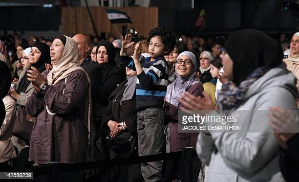 People applaud to welcome Swiss Muslim intellectual and professor Tariq Ramadan during a meeting focused on 'Faith and Resistance Reform and...