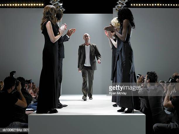 People applauding fashion designer on catwalk
