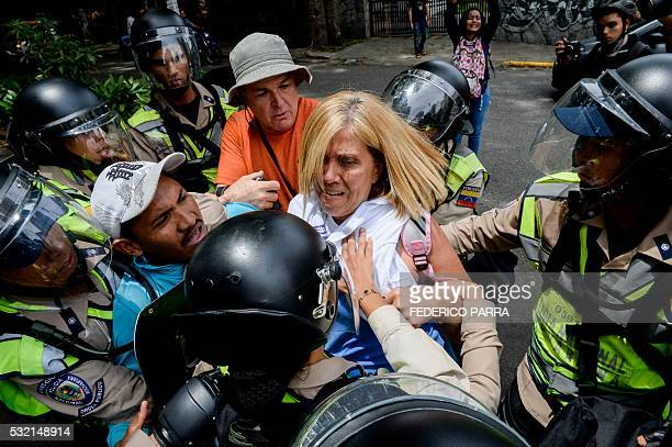 TOPSHOT People are arrested during a protest against new emergency powers decreed this week by President Nicolas Maduro in Caracas on May 18 2016...