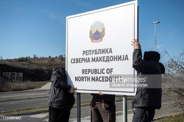 People are at work to set up a sign reading 'Republic of North Macedonia' at the Macedonia-Greece border near Gevgelija on February 13, 2019. - The...