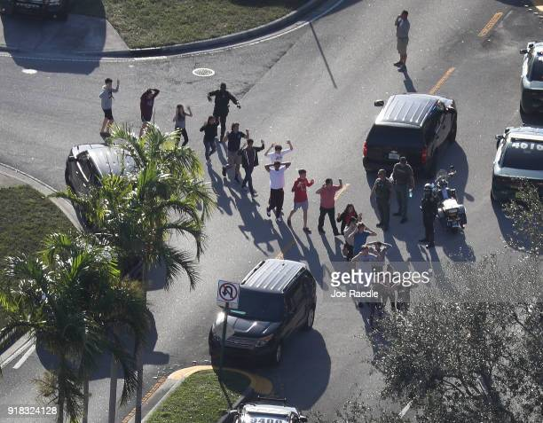 People are brought out of the Marjory Stoneman Douglas High School after a shooting at the school that reportedly killed and injured multiple people...