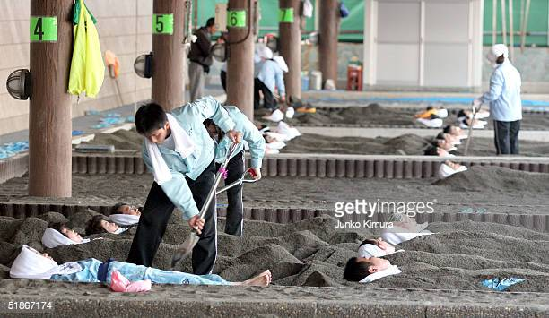 People are buried to their neck in black sand for a hot sand bath on December 16, 2004 in Ibusuki, Kagoshima Prefecture, Japan. Japanese have been...