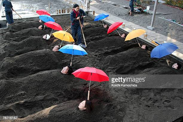 People are buried to their neck in sand bath at Beppu Seafront Sand Spa on December 3, 2007 in Beppu, Oita, Japan. Customers are buried in natrually...