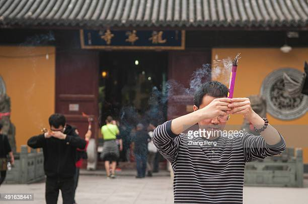 People are burning incense and praying before Longhua Temple Shanghai After reform and opening policy Buddhism has developed fast in China and...