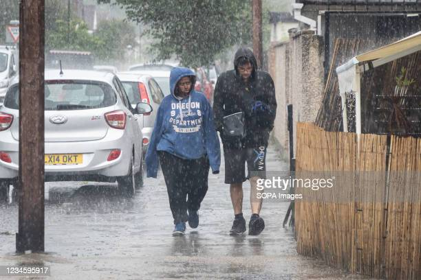 People are caught in a heavy downpour in Hounslow. The Met Office has issued thunderstorm warning with flash flooding over parts of the United...