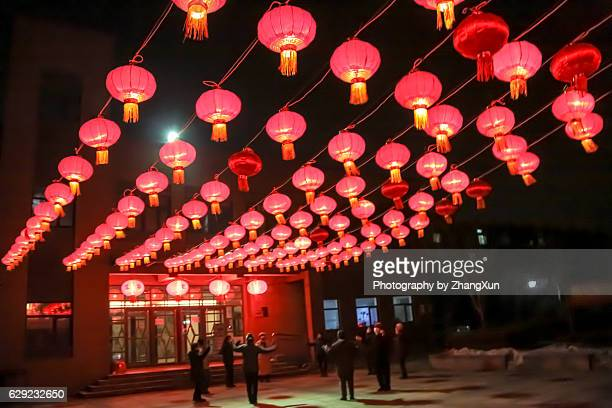 People are dancing celebrating Chinese new year under Chinese lanterns in Shenyang, Liaoning, China.