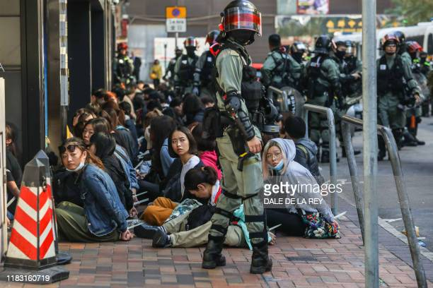 People are detained by police near the Hong Kong Polytechnic University in Hung Hom district of Hong Kong on November 18, 2019. - Pro-democracy...