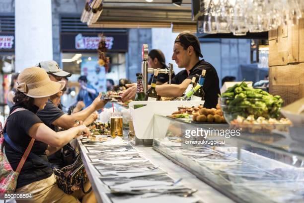 People are eating seafood in La Boqueria Market, Barcelona
