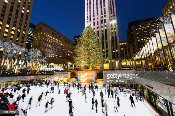 People are enjoying ice-skating at The Rink at Rockefeller Center at night in Christmas Holidays season 2016 New York at night. Rockefeller Center are decorated and illuminated for Christmas.