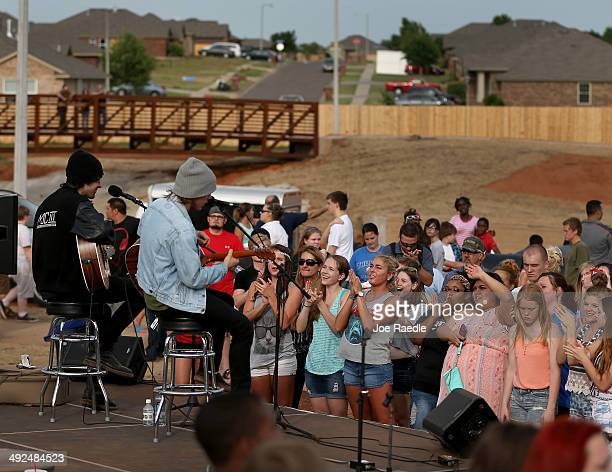 People are entertained at a Moore Recovery Celebration by the band New Hollow in a park that was rebuilt after the neighborhood was devastated by a...