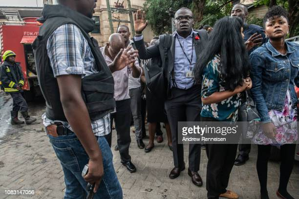 People are escorted by security personnel from the Dusit Hotel on January 15 2018 in Nairobi Kenya A current security operation is underway after...