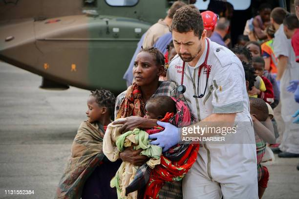 People are escorted to safety by aid workers at the airport of the coastal city of Beira in central Mozambique on March 19 after the area was hit by...
