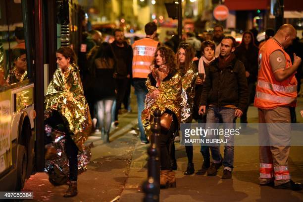 People are evacuated by bus, near the Bataclan concert hall in central Paris, on November 14, 2015. More than 100 people were killed in a mass...