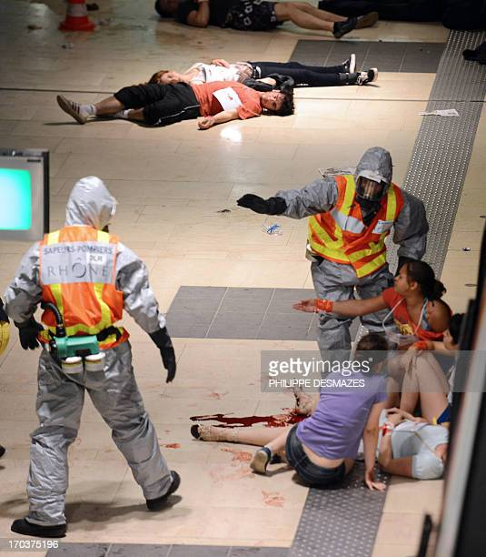 People are evacuated by rescue workers during a chemical terrorist attack drill in the subway during the 'EU URBAN CREATS 2013' community exercises...