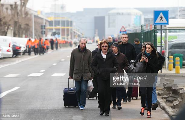 People are evacuated from Brussels Airport, in Zaventem, on March 22, 2016. After at least 13 people have been killed by two explosions in the...