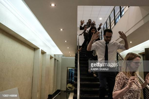 People are evacuated from the building after a bomb blast from the office block attached to DusitD2 hotel in Nairobi Kenya on January 15 2019 A huge...