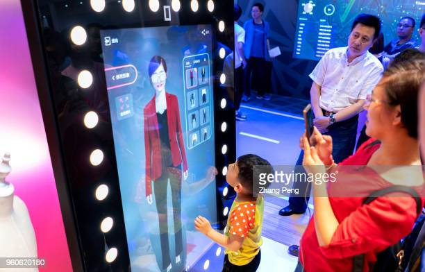People are experiencing the AI fitting technology while shopping on Tmallcom or Taobaocom in the future Alibaba show its smart technology in...