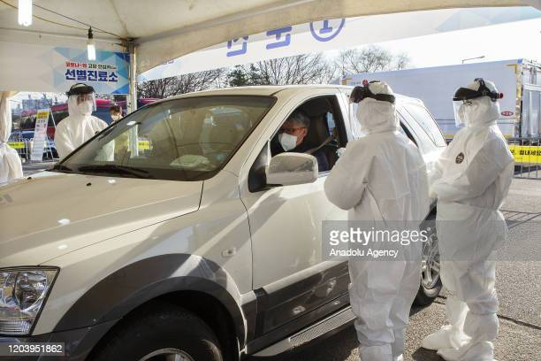 People are getting checked in their vehicles at a drive-through coronavirus clinic on February 27 in Goyang, South Korea.
