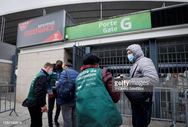 People are guided upon their arrival to be vaccinated against Covid-19 at a vaccination centre set up at the Stade de France , in Saint-Denis,...