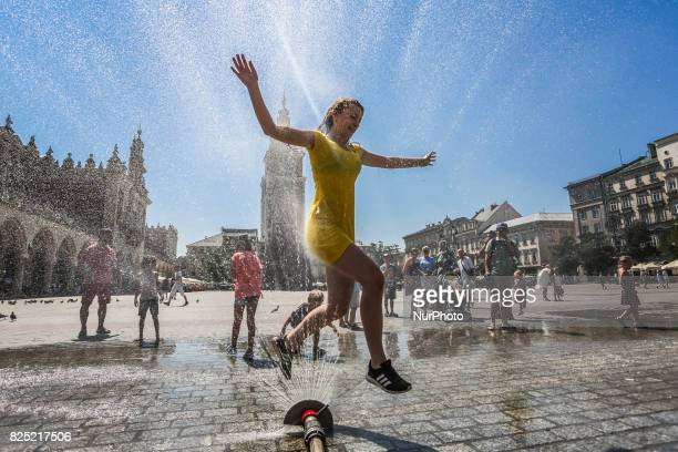 People are having fun running through a water sprinkler in the Main Square in Krakow's Old Town as heat wave continues and temperatures reach 36...