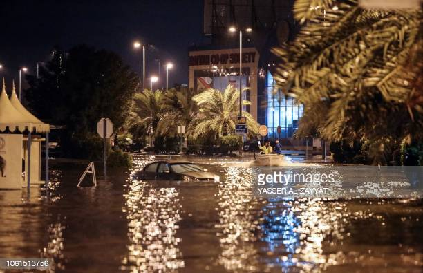 People are having fun with a boat on the flooded main road of the Daeya area of Kuwait city late on November 14 following heavy rain in the Gulf...