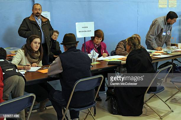 People are helped with same day registration as voters cast their ballots at the Bishop Leo O'Neil Youth Center on November 6 2012 in Manchester New...