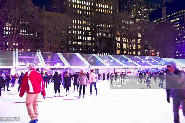 people are ice skating during the holiday season on the illuminated  rink in bryant park  in new york city, new york,usa - bryant park stock pictures, royalty-free photos & images