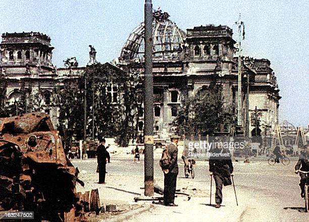 People are in the streets near the Reichstag which has suffered considerable damage during World War II and was partially destroyed during the battle...