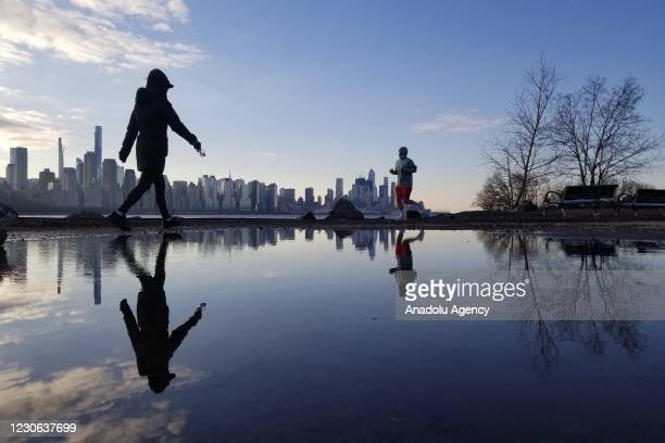 People are jogging by the Hudson River during sunrise in New York, United States on January 17, 2021.
