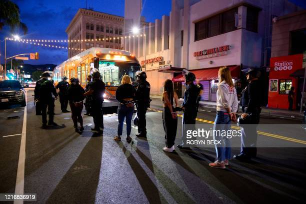 People are loaded onto buses by police officers after being arrested in Hollywood, California, June 1 as a third night of curfews followed days of...