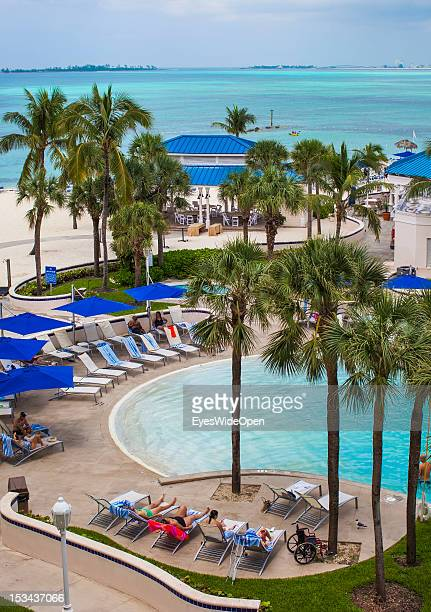 People are lying at a hotel pool close to the beach on June 15 2012 in Nassau The Bahamas